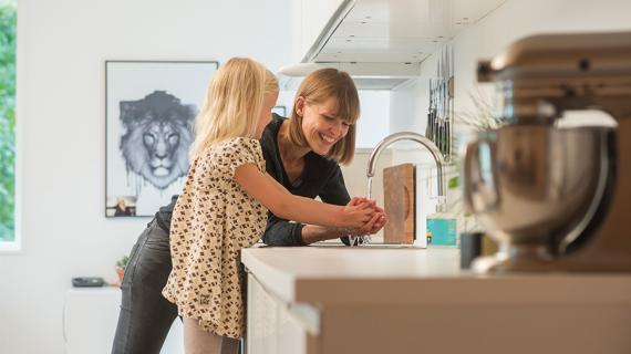 Mor og datter vasker hænder sammen