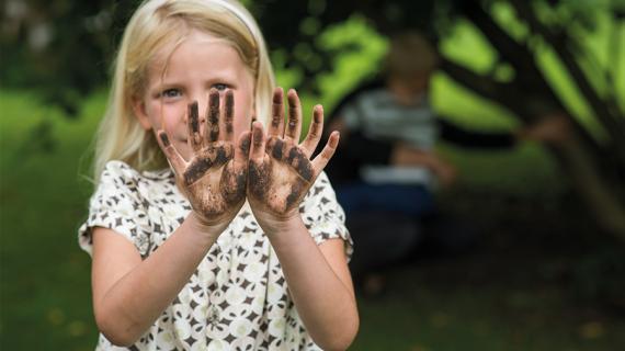 Pige med beskidte hænder i haven