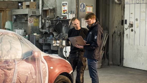 Miljømedarbejder og automekaniker står i autoværksted og kigger sammen på pc.