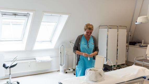 Speciallæge i Plastikkirurgi, Mette Rostgaard Krag,  fremviser affaldsspand til rent emballage i operationsstuen.