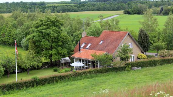 Hus med grønne marker. Deokrativt foto ift. energioptimering af hjemmet.