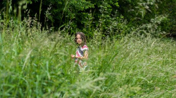 Pige i højt græs kigger på fotograf