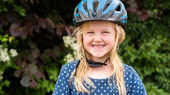 Pige med cykelhjelm på cirka 8 år smiler stort til kameraet.