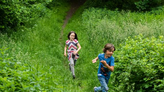"""Pige og dreng løber i grøn """"uplejet"""" natur"""