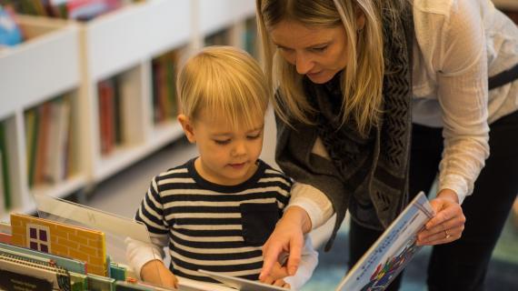 Mor kigger i billedbog med lille dreng