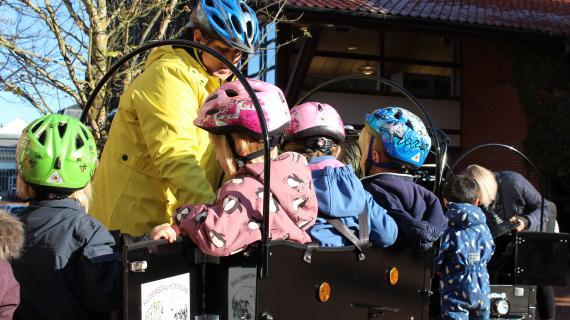 Børn med hjelme i ladcykel