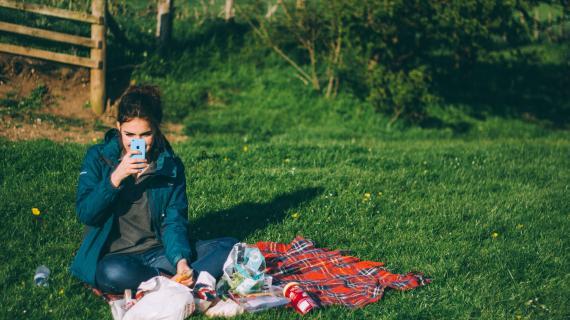 Kvinde sidder ude med telefon