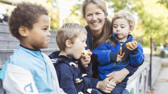 Pædagog og børn sidder udendørs