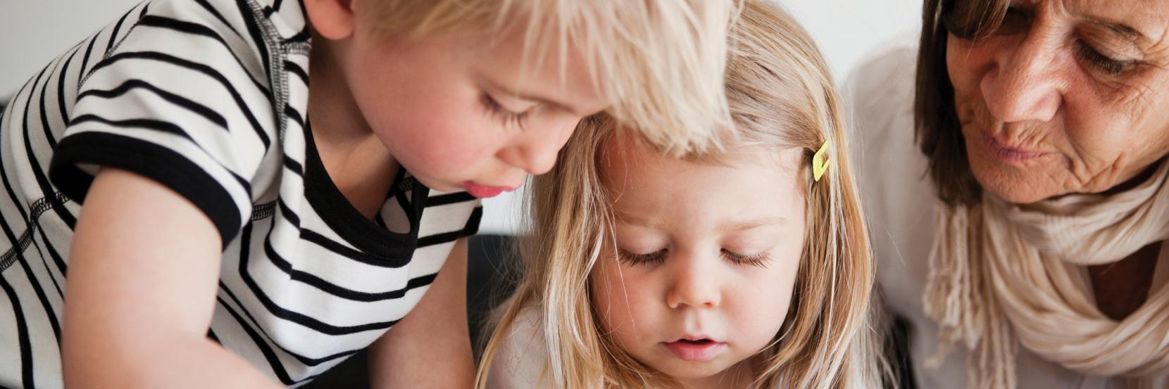 To børn i daginstitution kigger på iPad sammen med deres pædagog