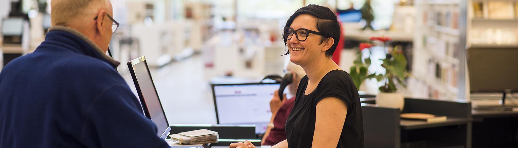 Bibliotekar hjælper kunde ved skranken