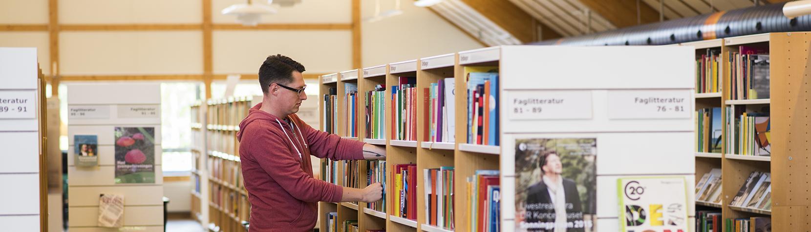 Mand leder efter bøger på bibliotek