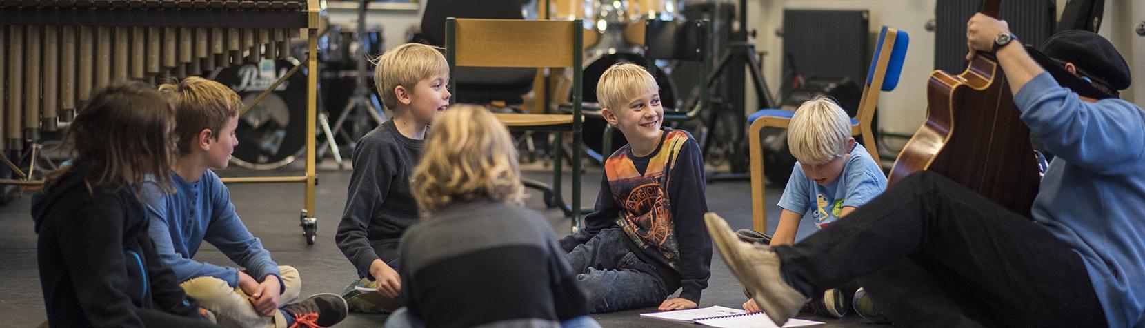Børn synger og spiller guitar i rundkreds