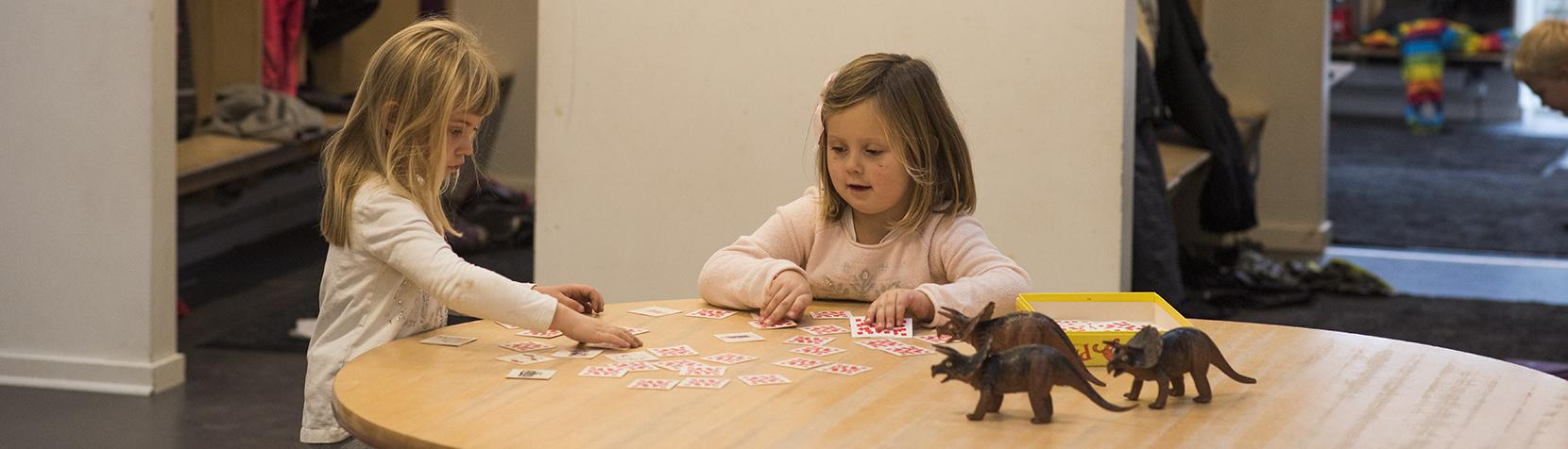 Piger leger med dinosaurere