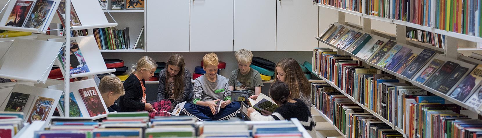 Skolebørn læser på bibliotek
