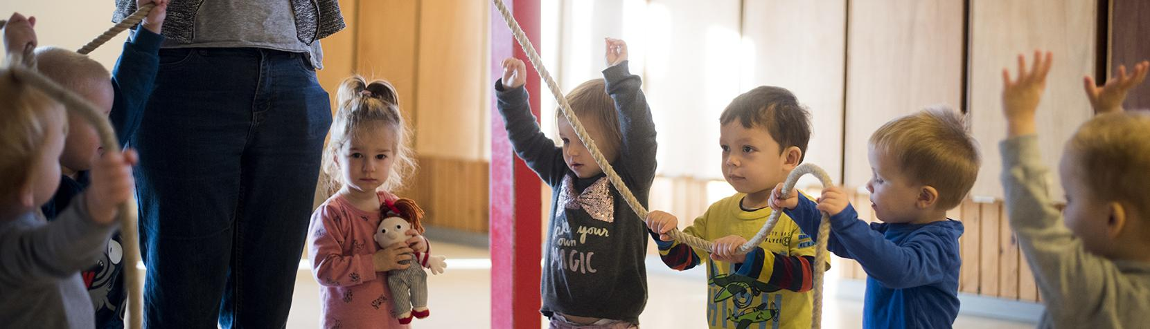 Børn og pædagog leger i rundkreds