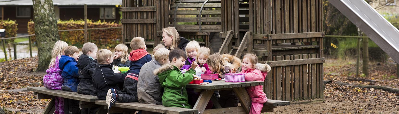 Børn spiser ved bord og bænke