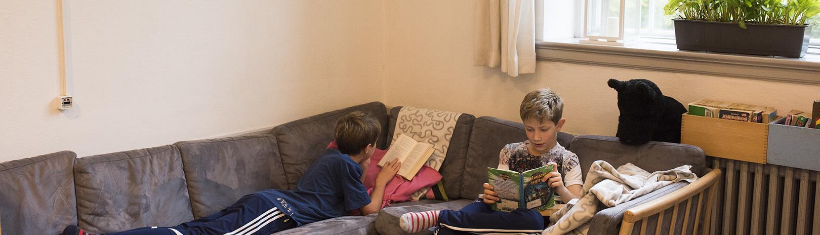Skoledrenge læser i sofa