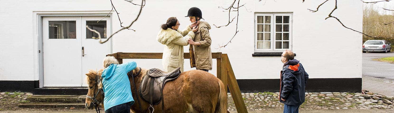 Billedet viser en pige, der får hjælp til at lukke ridehjelmen inden en ridetur