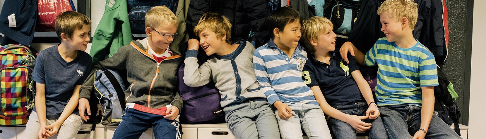 Drenge sidder i garberobe