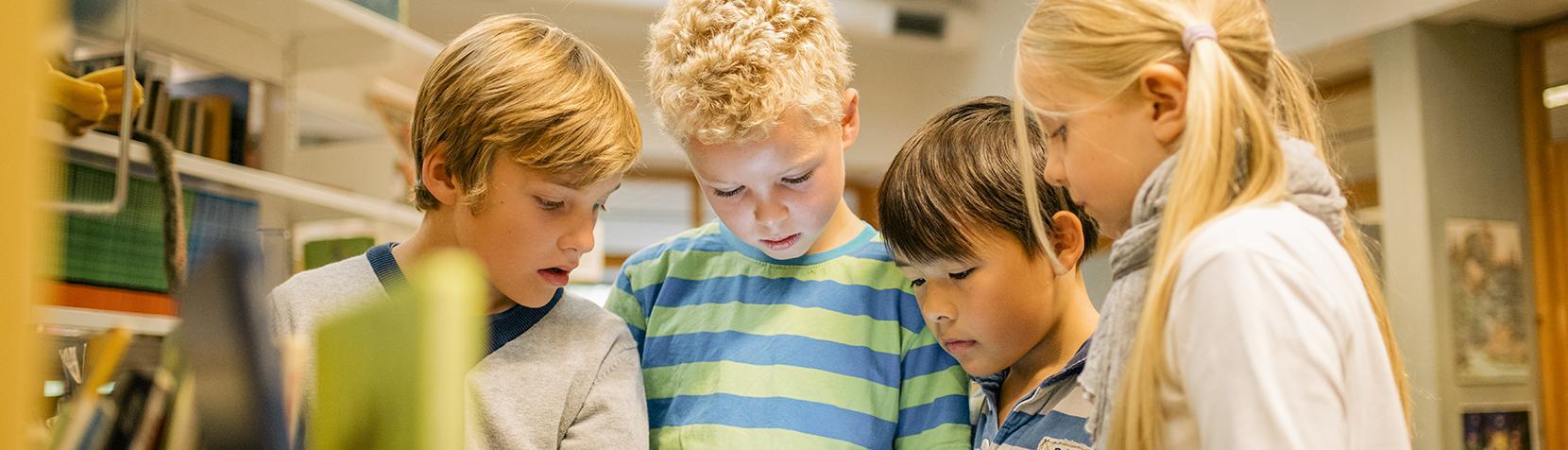 Skolebørn kigger på iPad