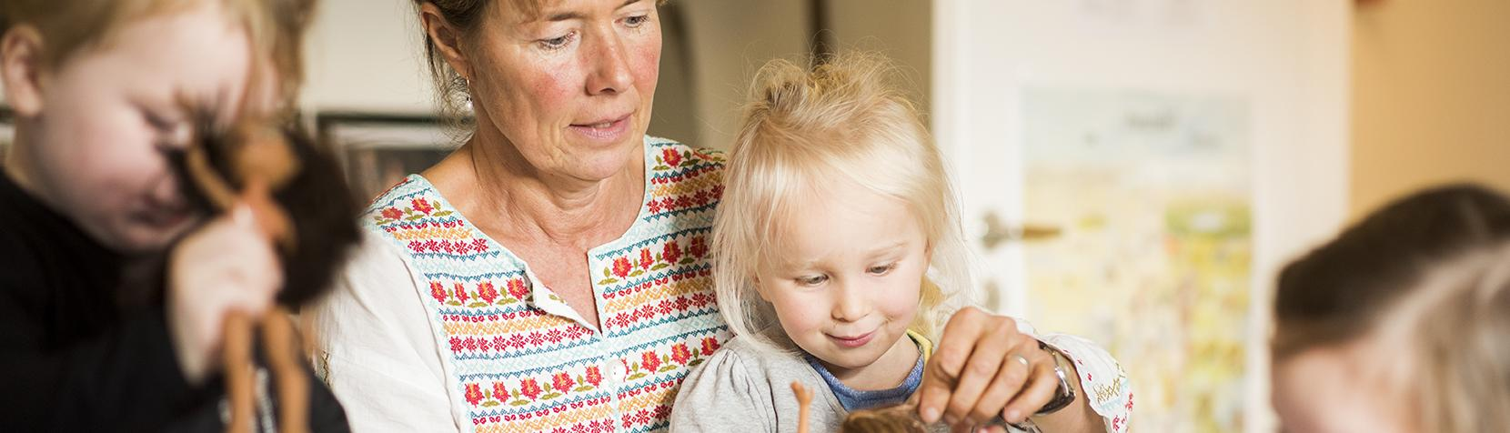 Børn og pædagog leger med dukker