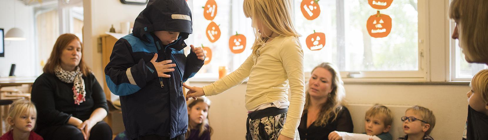 Børn og pædagoger leger i rundkreds