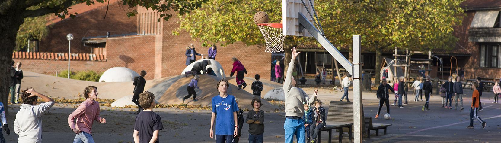 Drenge spiller basketball i skolegården