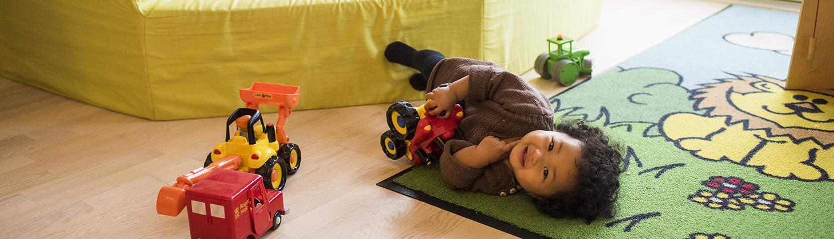 Lille pige tumler på gulvet