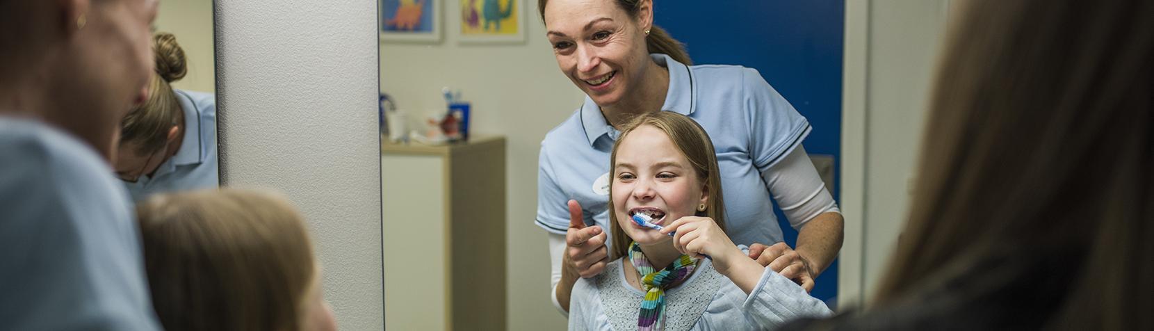Tandlægen instruerer i korrekt tandbørstning
