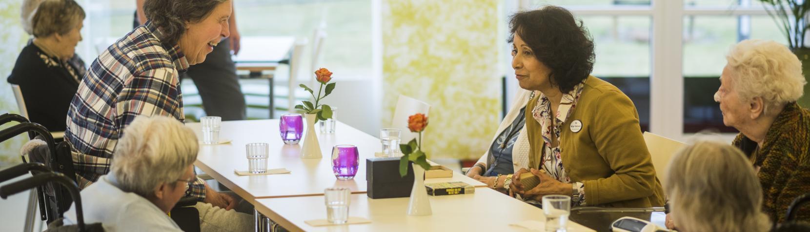 Dagligdagen på Byageren. Der sidder beboere og medarbejder rundt om et bord. De har en dialog om et emne som fanger alles interesse.