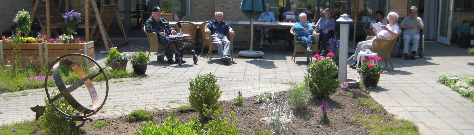 Billedet viser beboere fra Hus A, der nyder solen foran huset