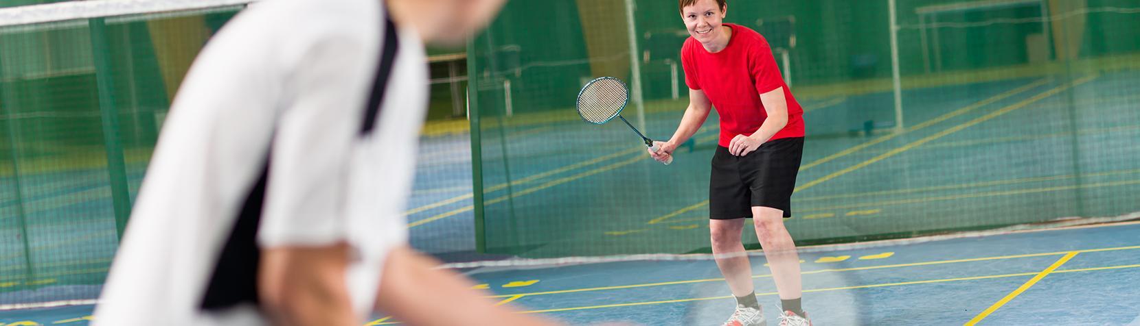 To der spiller badminton på en bane