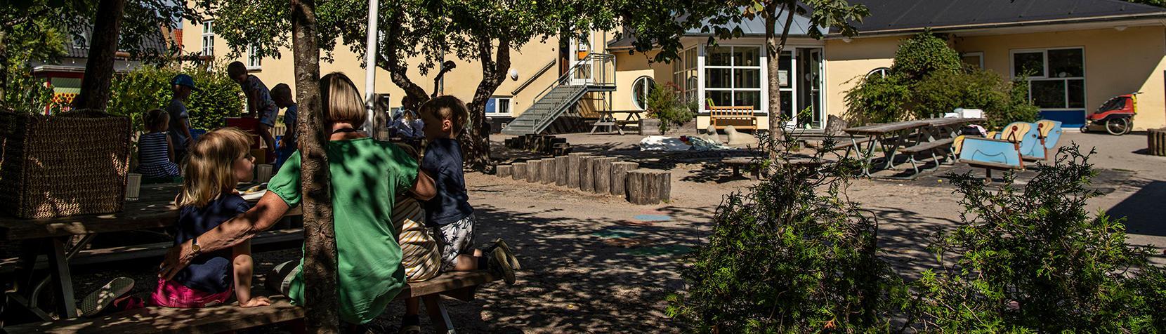 Børn sidder ved bord foran Børnehuset Abildgården