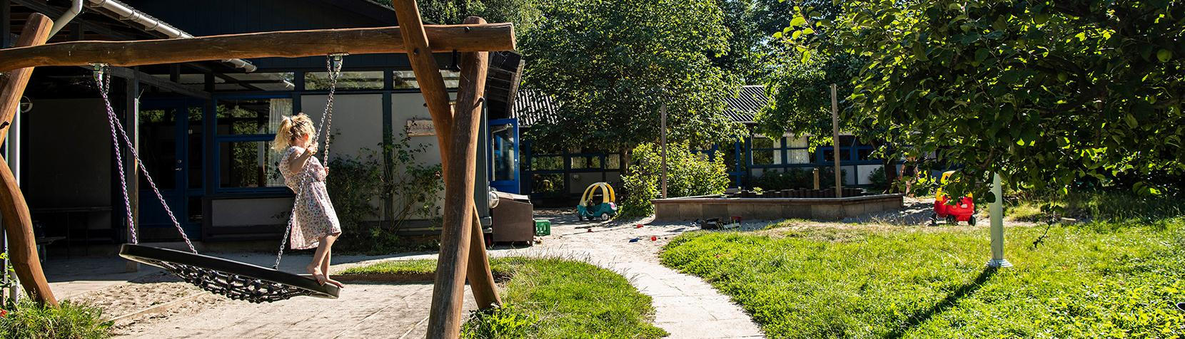 Pige gynger foran Børnehuset Ellesletten