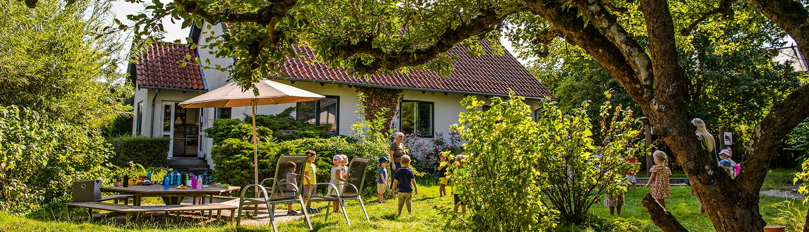 Skyttebjerg set udefra med børn på græsset