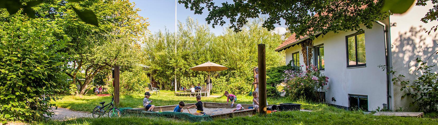 Børn leger i sandkasse foran Børnehuset Skyttebjerg