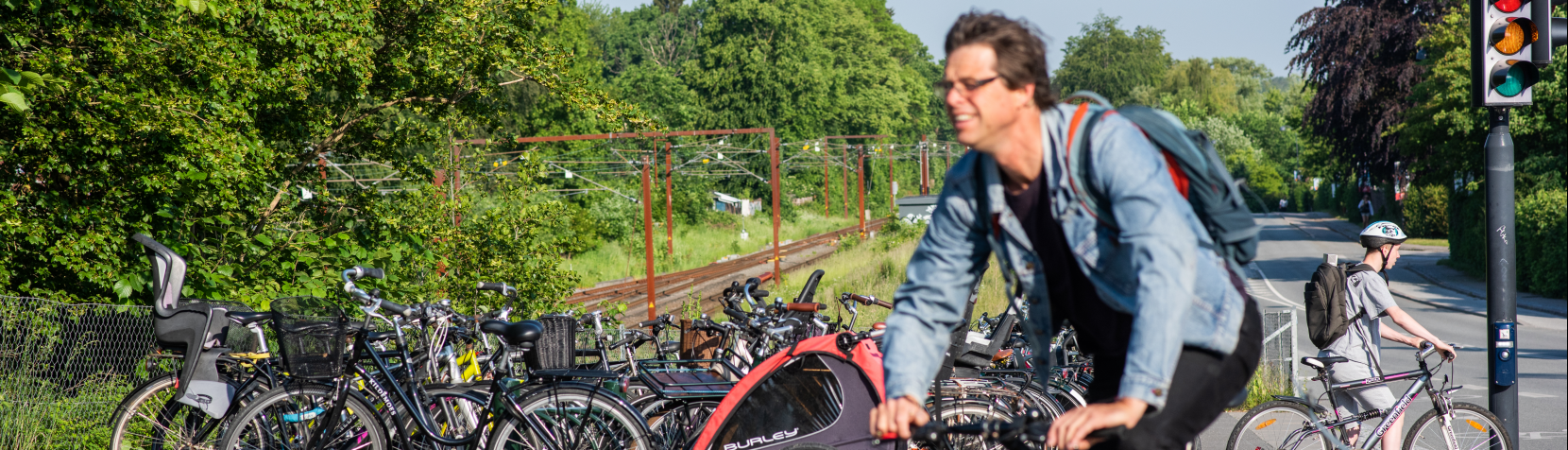 Cyklist ved parkerede cykler ved stationen
