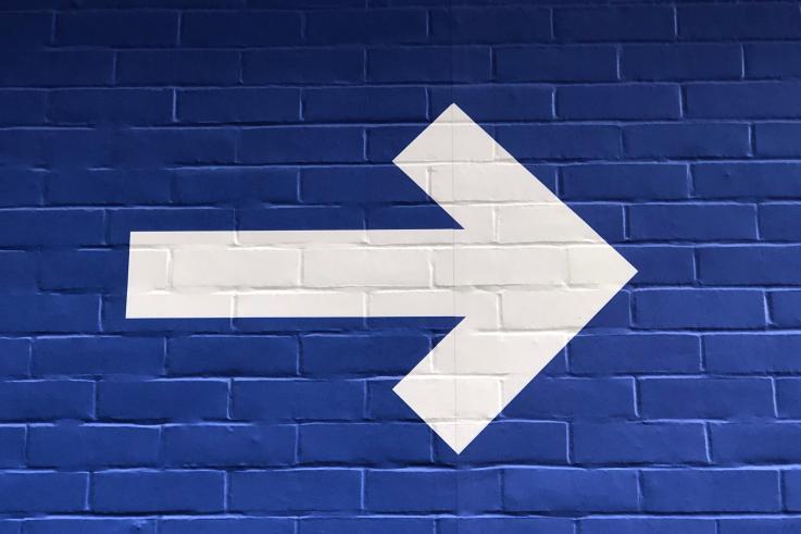 Hvid pil på blå baggrund