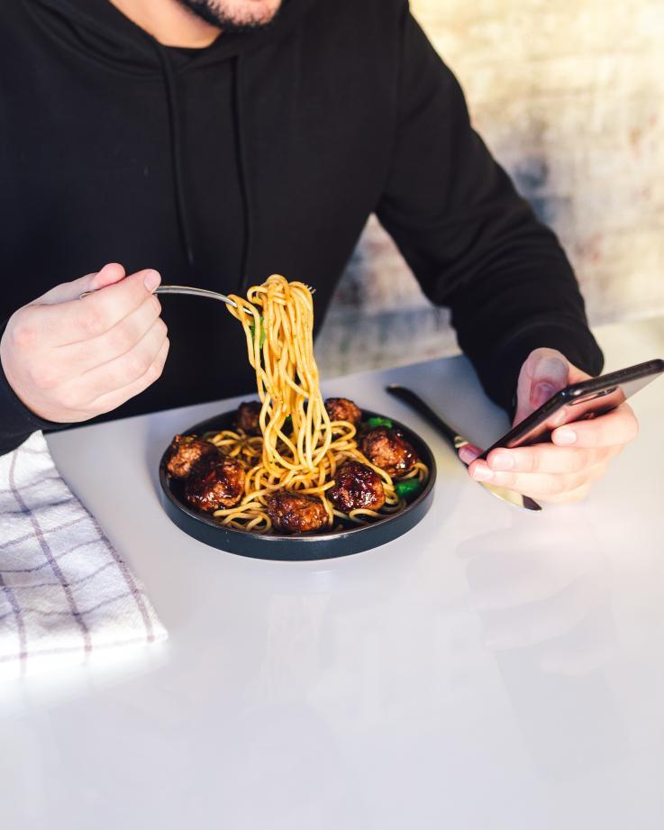 Spiser og holder telefon