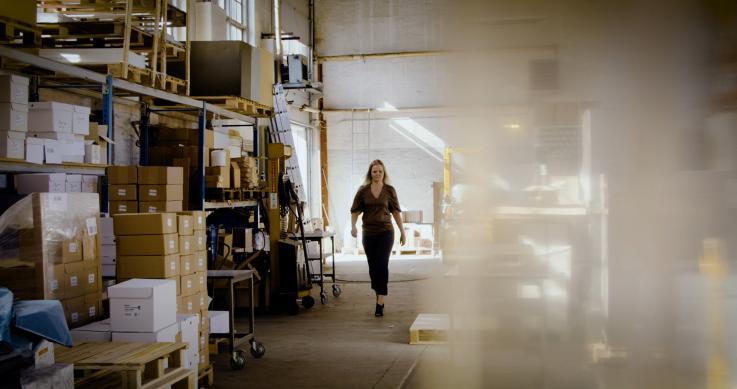 kvinde går gennem lagerhal