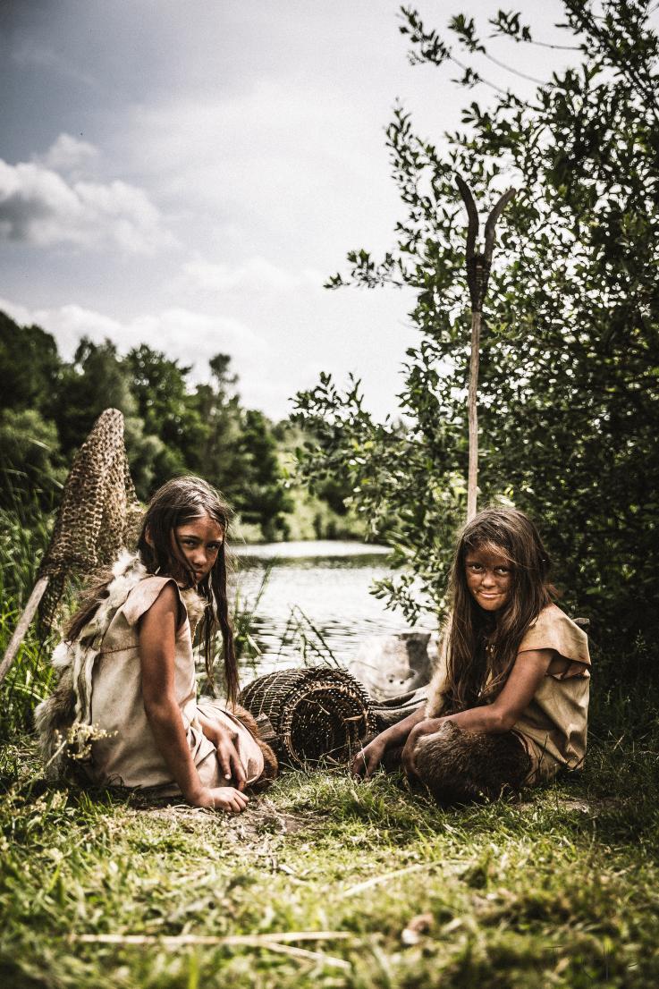 Stenalderpiger sidder ved sø