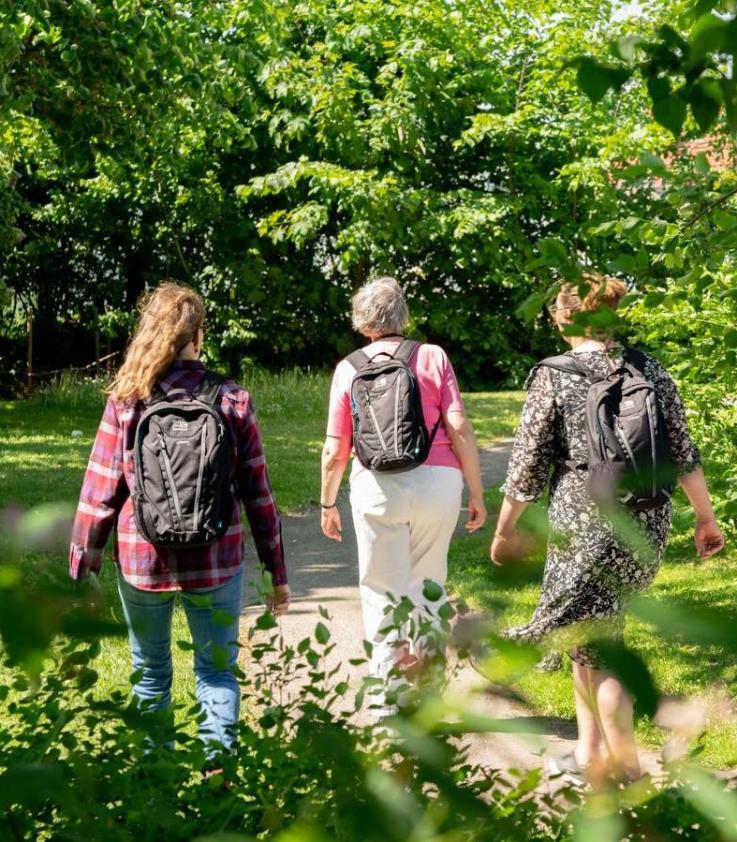 Mennesker ses bagfra med rygsække på vej ud i naturen