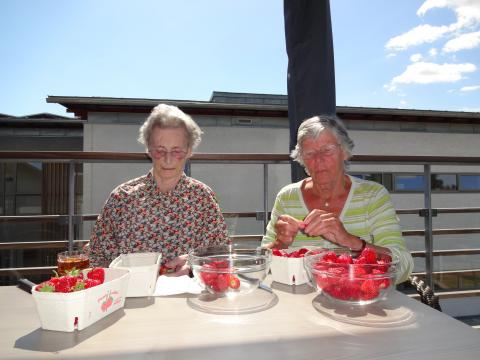 To kvinder spiser jordbær på terrassen