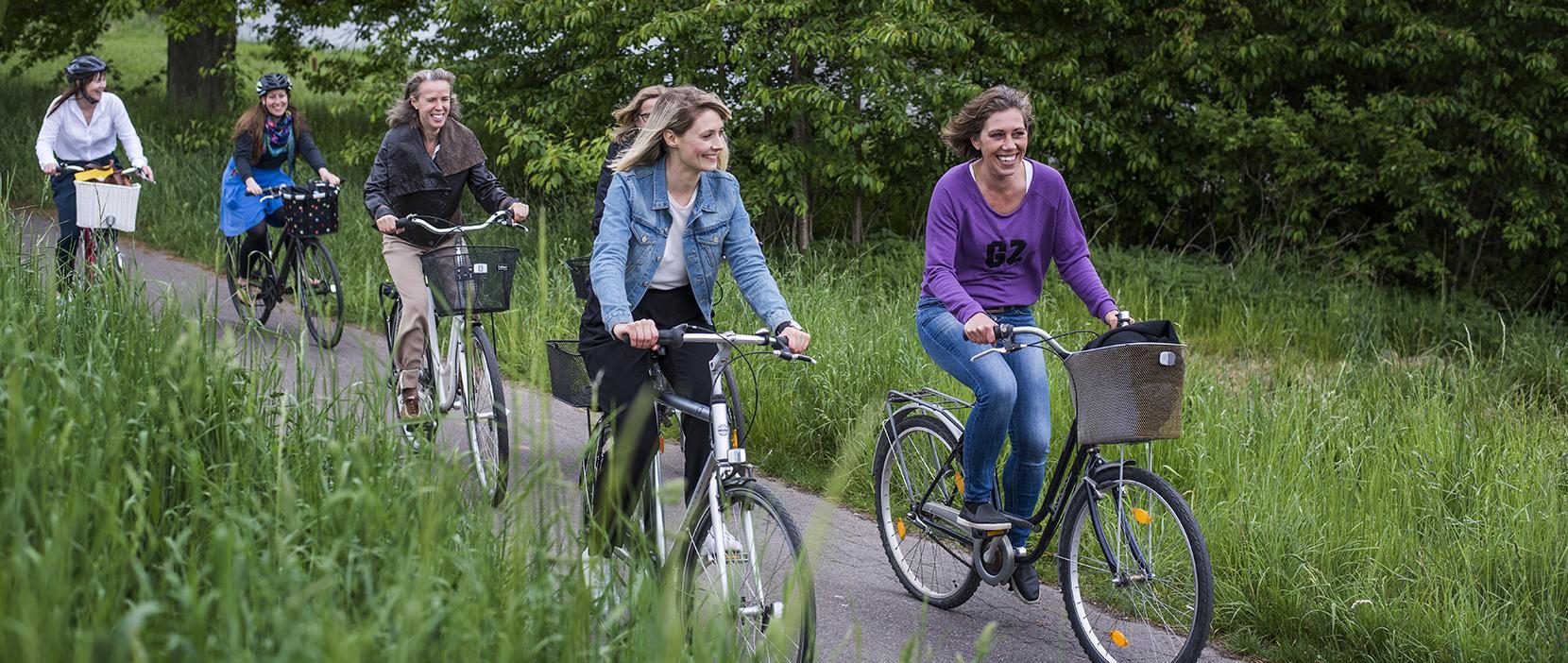 Kvinder på cykeltur i grønne omgivelser