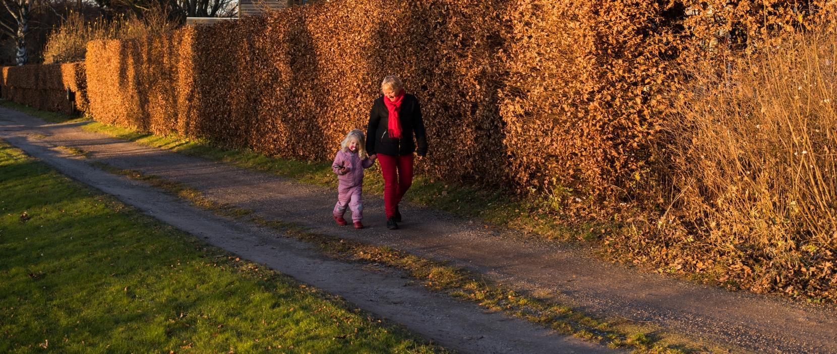 Mormor og barnebarn går tur i efteråret