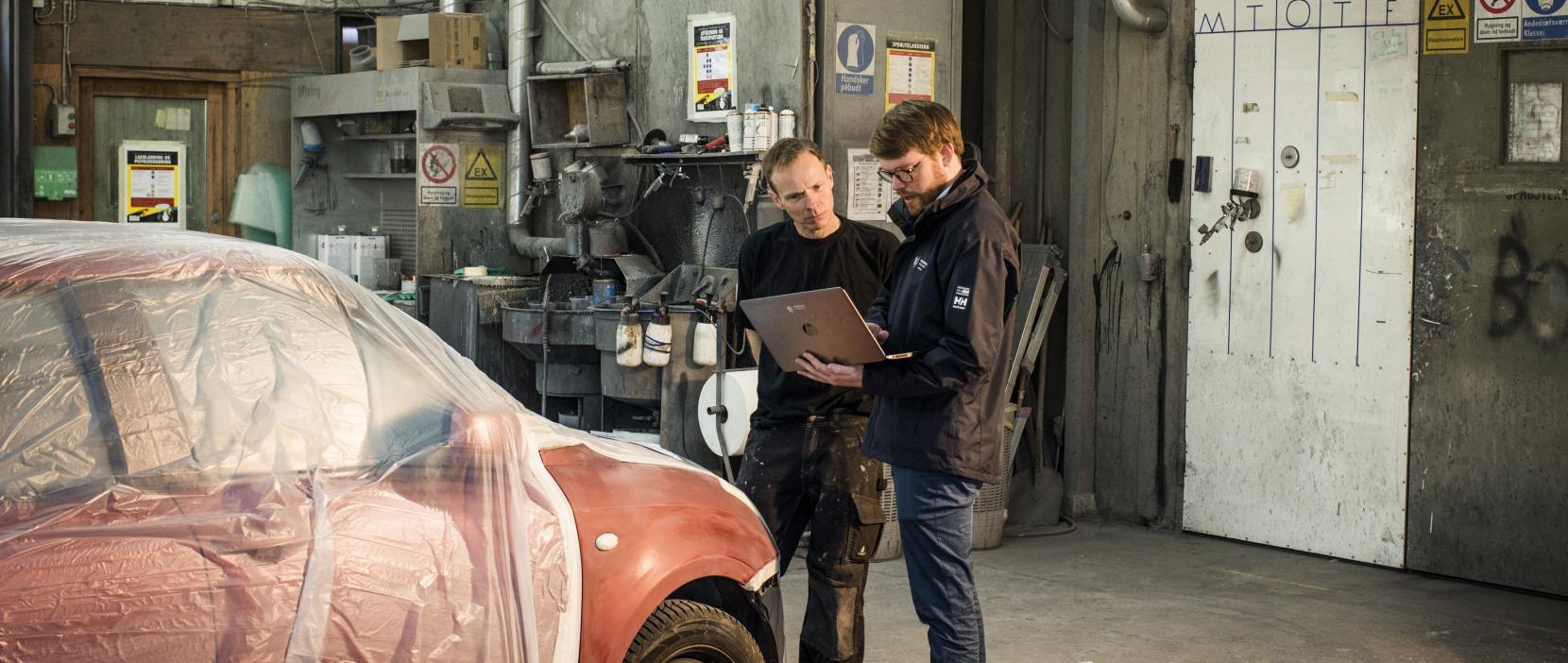 Miljømedarbejder og automekaniker står i autoværksted og kigger sammen på pc