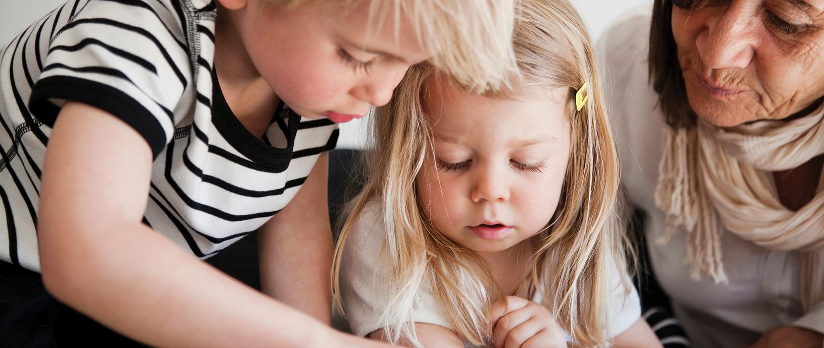 Pædagog og to børn kigger på iPad